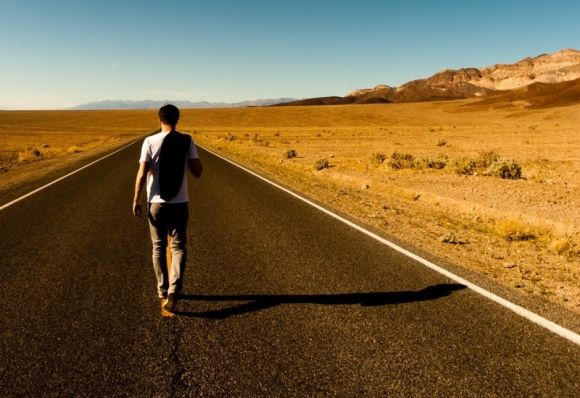 Guy walking down road traveling