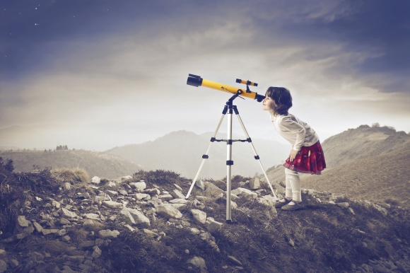 Little girl looking into a telescope in the mountains