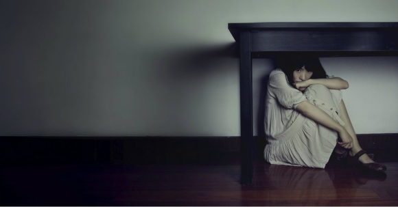 woman hiding under table