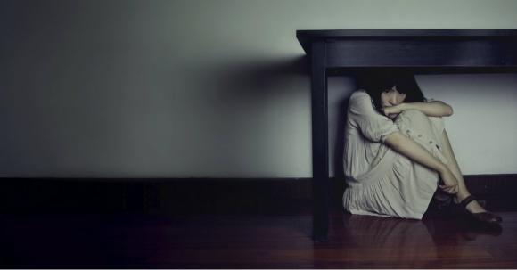 woman hiding under table