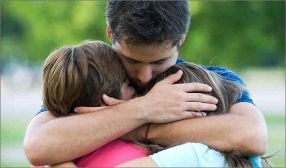 father hugging children